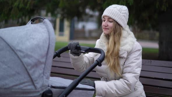 Cover Image for Junge Mutter mit neugeborenem Kind im Freien. Sie sitzt auf der Bank mit Baby schlafen im Kinderwagen
