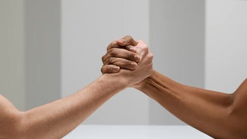 Two Hands Joining Together and Doing Arm Wrestling Isolated Over White Background in Slow Motion