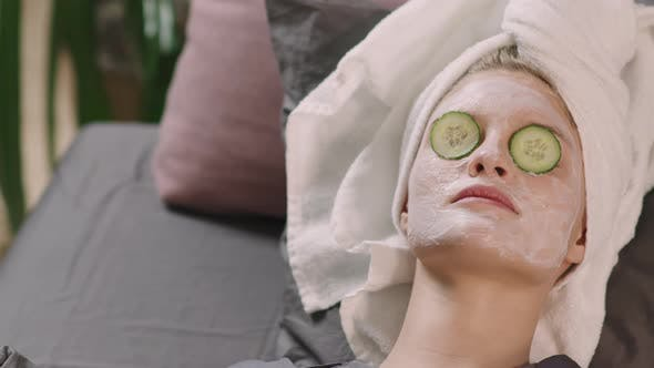 Girl In Facial Mask And Cucumber Slices On Mask