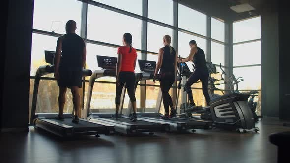 Thumbnail for Four People Young Men and Women Walking on Treadmills in the Fitness Room. Start Training Warm Up