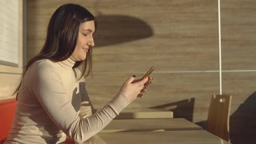 Young Brunette Woman Sitting in Cafe with Telephone, Virtual Communication