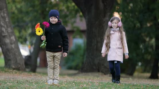 Little Girl Approached to the Little Boy in the Park