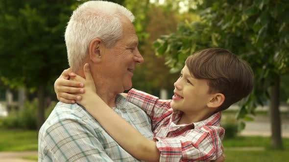 Thumbnail for Little Boy Holds His Hands Behind His Grandpa's Neck