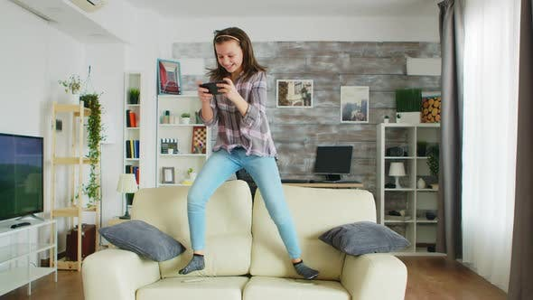 Thumbnail for Little Girl Jumping on the Couch in Living Room