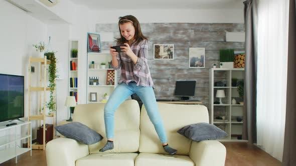 Kleines Mädchen Springen auf der Couch im Wohnzimmer