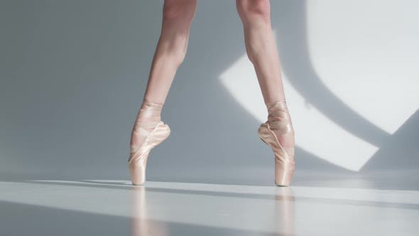 Thumbnail for Ballerina Dancing Ballet, Feet in Pointe Tied with Ribbons Closeup on White Background.