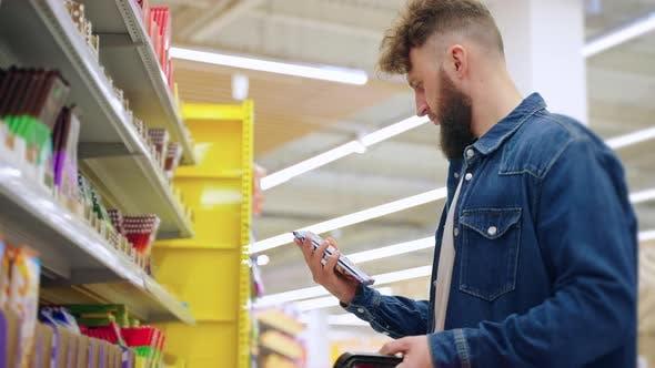 Supermarket Buyer Choosing Chocolate Bar