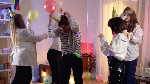 Joyful Millennial Men and Women Fighting with Balloons at Birthday Party