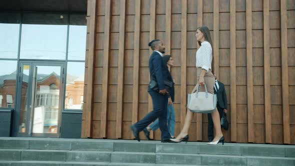 Side View of Beautiful Young Businesswoman Walking Outdoors Along Modern Office Center