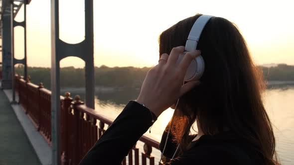 Thumbnail for Slow Motion Scene of Pretty Woman Putting on the Headphones and Looking at the Sunrise. Close Up