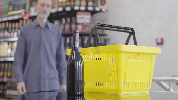 Adult Caucasian Man Coming To the Counter in Liquor Shop, Putting Bottle of Red Wine Into Yellow