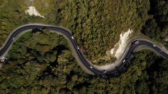 Thumbnail for Aerial View of Car Driving Along The Winding Mountain Pass Road Through The Forest Trees. Autumn