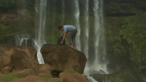Guy with Backpack Stands on Rock Drinks Water By Waterfall