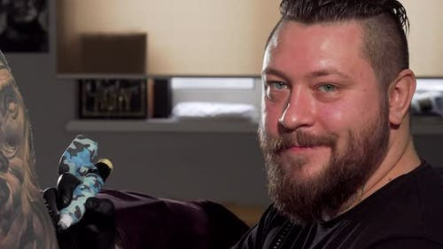Cheerful Bearded Tattooist Smiling To the Camera While Working