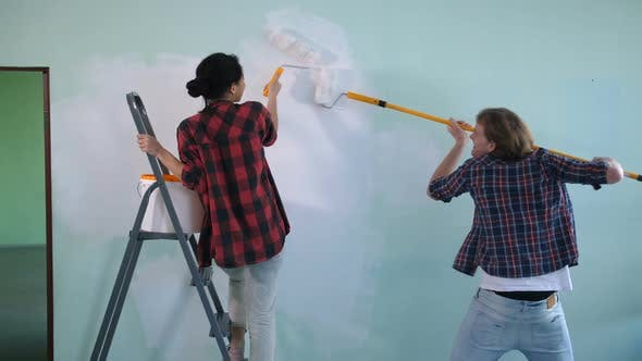 Thumbnail for Joyful Couple Painting Interior Wall in New House