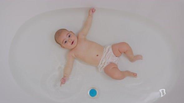 Glückliches Baby Baden. Fröhliches Kind von fünf Monaten in Wasser.