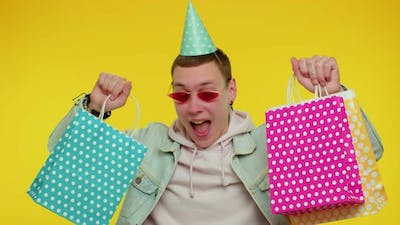 Teen Man Showing Shopping Bags Advertising Discounts Low Prices Shopping on Black Friday Holiday