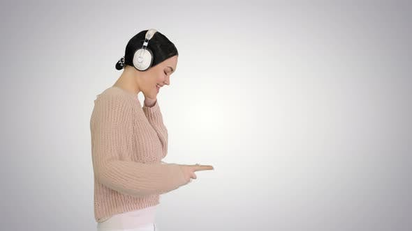 Smiling Female with Headphones Walking and Enjoying the Music on Gradient Background