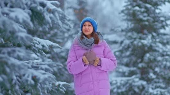 Nettes Mädchen geht durch den Winterwald die Kiefern sind im Schnee