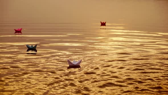 Thumbnail for Floating Paper Boats on the Water at Sunset