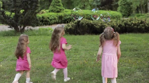 Thumbnail for Happy Little Girls Playing in Garden and Playing Bubbles