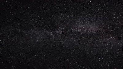 Night Sky with Stars, Satellites. Milky Way Passing in Long Exposure Timelapse. Beautiful Panorama