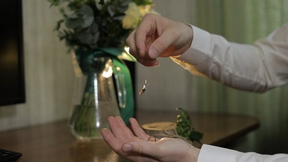 Thumbnail for Groom in a White Shirt Drops Wedding Rings To the Palm of His Hand. Man Touches the Rings