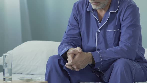 Thumbnail for Old Man Sitting in Pajama on Bed with Pills in Bowl on Night Table Depressed