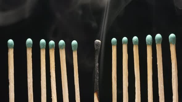 Thumbnail for Smoke of single burned matchstick between row of new matchsticks