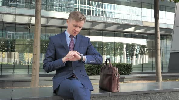 Thumbnail for Businessman Using Smartwatch for Browsing Outside Office