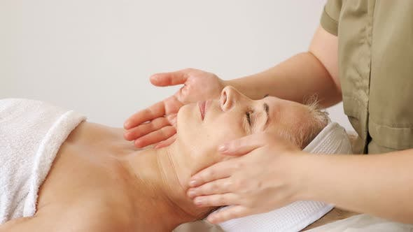 Spezialist macht eine Gesichts- und Nackenmassage zu einer Frau in einem Schönheitssalon