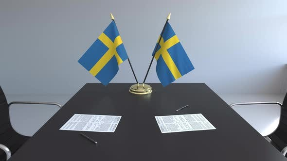 Flags of Sweden and Papers on the Table
