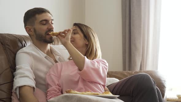 Thumbnail for Adult Woman Feeding Her Husband with Tasty Homemade Pizza Sitting on Leather Sofa. Happy Married