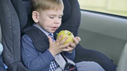 Kid Eating Apple in Car Seat