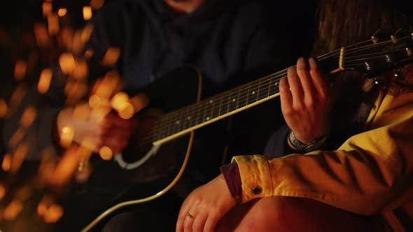 Thumbnail for Playing guitar at a campfire