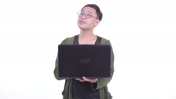 Thumbnail for Happy Japanese Man with Eyeglasses Thinking While Using Laptop