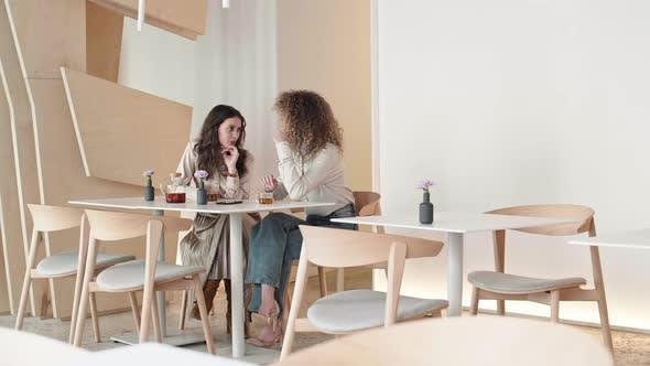 Two Women Gossiping in Cafe