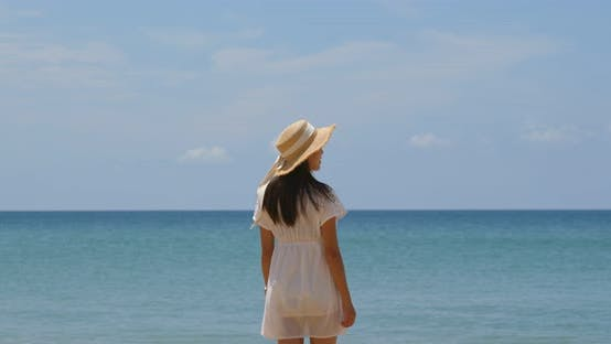 Woman with straw hat look at the sea