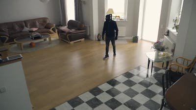 The Thief in Black Clothes and Balaclava Walking in the Large Living Room