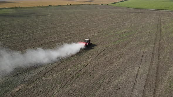 The Tractor Spreads Fertilizer On The Field
