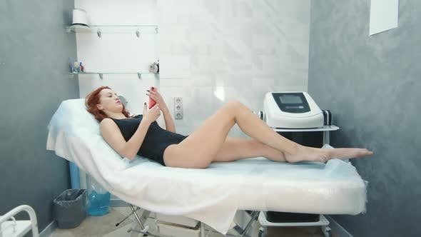 A Woman Is Lying on a Couch in a Beauty Salon and Waiting for a Procedure To Reduce Cellulite