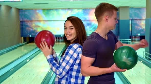 Thumbnail for Junge und Mädchen drehen Gesicht zu Gesicht bei der bowling
