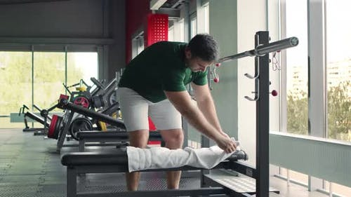 Man Laying Towel on Barbell Bench Before Workout, Personal Hygiene Concept