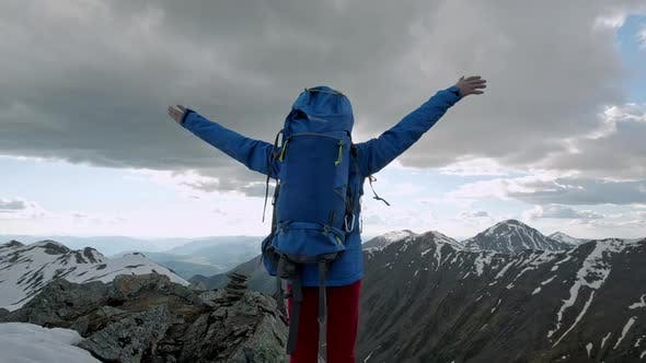 Thumbnail for Young Happy Woman with Backpack Standing on a Rock with Raised Hands and Looking To a Valley