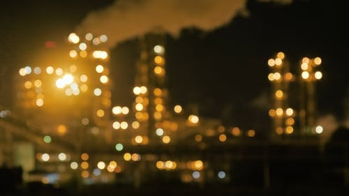 Oil Refinery Plant Shines at Night. Blurred Background