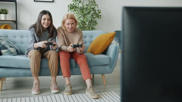 Joyful Teenager Playing Video Game with Mature Mother Enjoying Leisure Time at Home