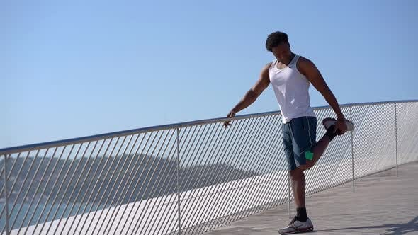 Thumbnail for Happy Athletic Man Stretching Leg at Sunny Day