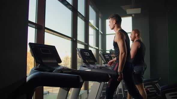 Thumbnail for Men Walk on Treadmills in the Fitness Room. A Group of People Walking on Treadmills Near a Large