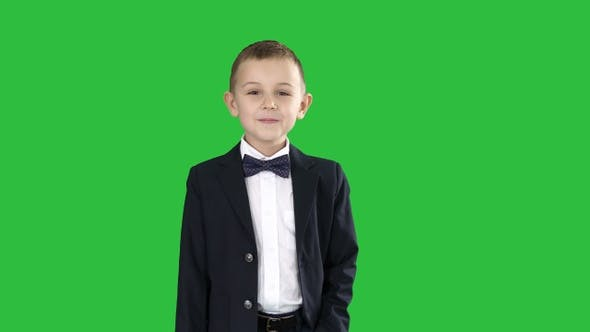 Boy in formal costume walking with a hand in pocket on