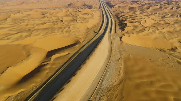 Thumbnail for Aerial view above of train rail crossing vast desert, U.A.E.